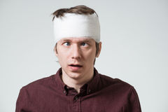 Man with bandage on his head. Cockeyed young man with bandage on his head. Image related with treatment of the wounds Royalty Free Stock Photo