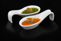 Cockles in green and red vegetable soup. Two small white porcelain spoons containing some red and green vegetable soup and one cockle inside each, on a black royalty free stock photography
