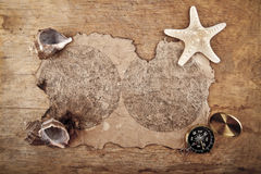 Cockleshells, starfish, compass and old paper. On a wooden background Stock Images