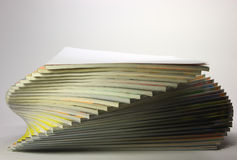 Cockling pile of magazines. With white cover on top Stock Image