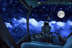 Cockpit in cloudy sky at night. Helicopter cockpit in a cloudy sky at night, with stars and full moon stock photos
