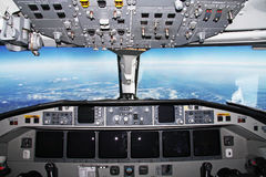 Cockpit in flight. Cockpit of an airliner in flight with mountains below Stock Photo