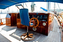 Cockpit inside a boat with a wood wheel. Royalty Free Stock Image