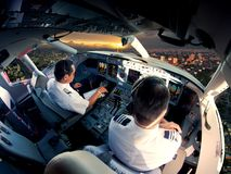 Cockpit of modern passenger jet aircraft. Pilots at work. Aerial view of modern city business district and sunset sky stock image