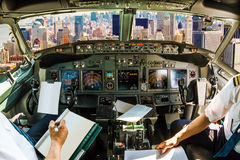 Cockpit on New York. Cockpit and board of an airplane flying on New York skyline of United States of America.. Pilots arms and blank white papers for copy space Stock Images