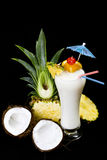 Cocktail. A decorated Pina Colada over black background, garnished with slice of pineapple and coconut Stock Photos