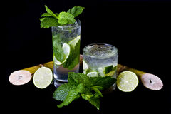 Cocktail. A Mojito and a Caipirinha over black background, garnished with mint leaves, lemon and Sugar cane Stock Image