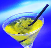 Cocktail. A glass with a yellow cocktail on a blue background stock image