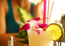 Cocktail. Exotic cocktail with orchid flower, straw and lime slice Royalty Free Stock Image