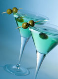 Cocktail. Martini cocktail with olives and blue background Royalty Free Stock Image