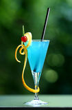Cocktail 841. Blue cocktail with blurry green background, beautifully arranged with a piece of lemon orange and a cherry Stock Image
