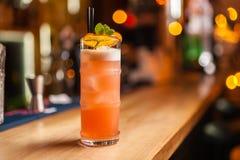 Cocktail alaranjado com a laranja secada na barra, fundo borrado foto de stock royalty free