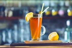 Cocktail alcoólico alaranjado em um vidro com limão e palhas em vagabundos imagens de stock