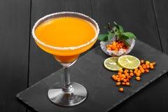 Cocktail alcoólico com espinheiro cerval de mar em um vidro no fundo escuro imagem de stock