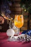 Cocktail alcoólico do inverno com tangerinas, suco e gelo no fundo decorado Natal imagens de stock royalty free