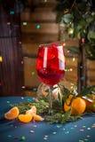 Cocktail alcoólico vermelho com gelo e laranja na tabela azul no fundo decorado Natal imagens de stock royalty free