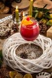 Cocktail alcoólico vermelho com gelo, laranja e cereja na tabela de madeira no fundo decorado Natal fotos de stock