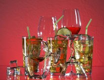 Cocktail and alcoholic drink. Glass with alcohol and ice on red background Stock Photos