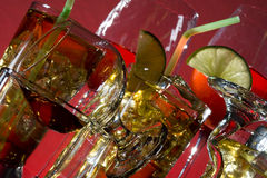 Cocktail and alcoholic drink. Glass with alcohol and ice on red background Stock Photography