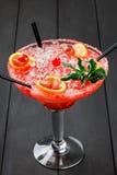 Cocktail alcolico freddo dell'anguria con l'arancia, la menta, il ghiaccio e l'uva in grande bicchiere di vino su fondo di legno  Fotografia Stock