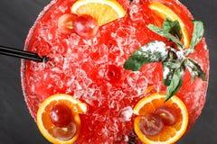 Cocktail alcolico freddo dell'anguria con l'arancia, la menta, il ghiaccio e l'uva in grande bicchiere di vino su fondo di legno  Fotografie Stock Libere da Diritti