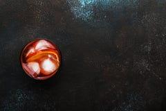 Cocktail alcoolique à la mode Negroni avec le genièvre sec, le vermouth rouge et amer rouge, l'orange et les glaçons Fond de comp photo stock