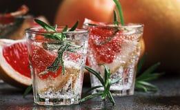 Cocktail alcoolique avec le pamplemousse, la soude, la glace, le genièvre et le romarin, fond foncé de compteur de barre de pierr image libre de droits