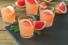 Cocktail alcoolique avec le verre de boissons de pamplemousse sur un conseil en pierre noir images stock
