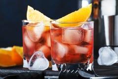 Cocktail alcoolique Negroni d'été avec le genièvre sec, le vermouth rouge et la tranche rouge et les glaçons amers et oranges r image stock