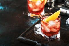 Cocktail alcoolique Negroni d'été avec le genièvre sec, le vermouth rouge et la tranche rouge et les glaçons amers et oranges r photo libre de droits