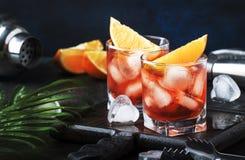 Cocktail alcoolique Negroni d'été avec le genièvre sec, le vermouth rouge et la tranche rouge et les glaçons amers et oranges r images libres de droits