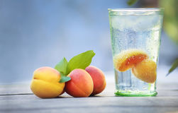 Cocktail with apricots on wooden table. Summer cocktail with pieces of fruit on wooden table Stock Image