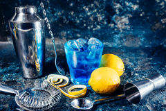 Cocktail as refreshment on bar counter, served cold. Long, alcoholic drink with lemon garnish Stock Images