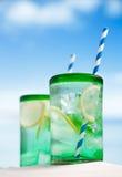Cocktail avec de la glace, le rhum, le citron et la menthe dans un verre sur la plage Images libres de droits