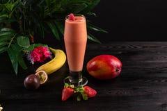Cocktail avec des fruits et des baies dans un verre grand sur un fond fonc? image stock