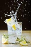 Cocktail avec le genièvre et le tonique. Éclaboussement images stock