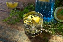 Cocktail avec le genièvre, le tonique et le citron bleus photographie stock
