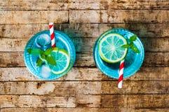 Cocktail azuis com o limão na tabela de madeira Imagem de Stock Royalty Free