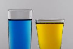Cocktail azuis e amarelos em vidros de tiro limpos Fotografia de Stock Royalty Free