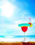 Cocktail on beach, blue sea and sky background Stock Photo
