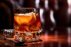 Old fashioned cocktail with orange slice, and orange peel garnish royalty free stock photography