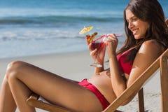 Cocktail bebendo da mulher feliz ao relaxar em sua cadeira de plataforma imagem de stock