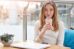 Cocktail bebendo fêmea louro novo de encantamento ao descansar após o trabalho no livro líquido, sentando-se no café, tomada do f imagem de stock