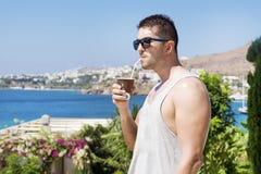 Cocktail bevente del giovane bello uomo in un giardino tropicale Fotografia Stock Libera da Diritti