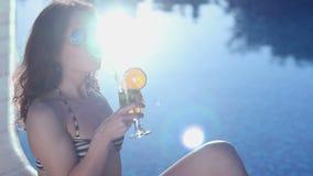 Cocktail bevente della ragazza felice, riflessione del sole che scintilla nello stagno archivi video