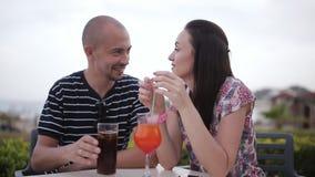 Cocktail beventi della donna e dell'uomo in un caffè all'aperto stock footage