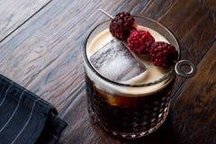Cocktail birra nera/scura con le more ed il ghiaccio su superficie di legno fotografia stock libera da diritti