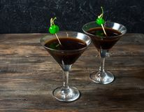 Cocktail Black Night Dancer with balsam and cola decorated by segments of a lemon and green cherry.  Stock Photo