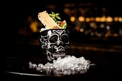 Cocktail in the black skull cup in mexican style. With pineapple, lemon, grapefruit and mint on the bar counter stock images