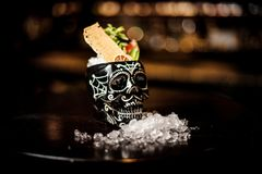 Cocktail in the black skull cup in mexican style with fruits. Cocktail in the black skull cup in mexican style with pineapple, lemon, grapefruit and mint on the stock photos